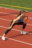 Frau im Sport-Büstenhalter, der Fahrwerkbein-Laufleine tut Stockfotos