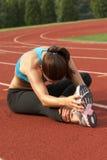 Frau im Sport-Büstenhalter, der Fahrwerkbein und Kniesehne lehnt und ausdehnt Lizenzfreies Stockfoto