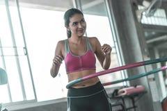 Frau im sportwear arbeitet mit Hula-Band in der Eignungsturnhalle für gesundes Lebensstilkonzept aus stockbild