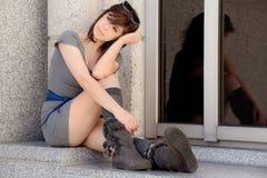 Frau im Stadtzentrum gelegen im Kleid und in den Stiefeln Stockbild