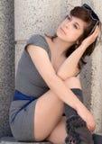Frau im Stadtzentrum gelegen im Kleid und in den Stiefeln Stockfoto