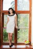 Frau im Stand des hübschen Kleids auf Schwelle Stockfotografie