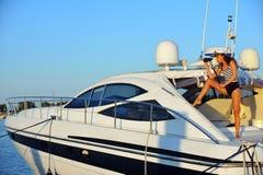 Frau im stilvollem Badeanzug und in Kapitänhut auf privatem Schnellboot im Urlaub Stockbilder