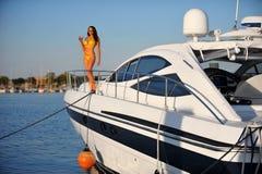 Frau im stilvollen Bikini, der auf der Plattform des Motorboots steht Lizenzfreie Stockfotos