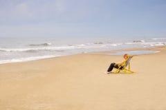 Frau im Stuhl auf Seestrand Stockfoto