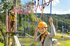 Frau, die auf Strickleiteradrenalinpark klettert Stockbilder