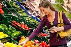 Frau im Supermarkt kauft Gemüse Stock Foto's