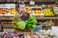 Frau im Supermarkt Schönes Einkaufen der jungen Frau in einem Supermarkt und in einem kaufenden frischen organischen Gemüse stockbild