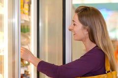 Frau im Supermarktgefriermaschinekapitel stockfotos