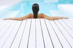 Frau im Swimmingpool, der auf Poolside stillsteht Stockfotografie