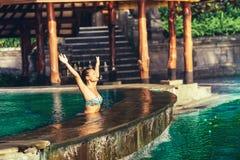 Frau im Swimmingpool, in der Schwimmen und im Ein Sonnenbad nehmen auf einem goldenen Licht des Sonnenaufgangs Stockbild