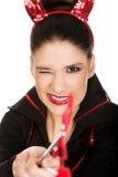 Frau im Teufelkostüm blinkt Auge Lizenzfreie Stockfotografie
