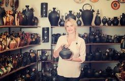 Frau im Tonwarenshop, der Topf wählt lizenzfreies stockfoto