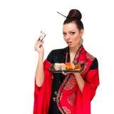 Frau im traditionellen roten Kleid mit Sushi Lizenzfreie Stockfotos