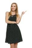 Frau im Tupfenkleid zeigend auf leeren Exemplarplatz Lizenzfreie Stockfotografie