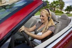 Frau im umwandelbaren Auto auf Bluetooth Kopfhörer Stockfoto