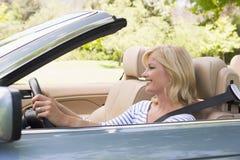 Frau im umwandelbaren Autolächeln Stockfotografie