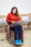 Frau im ungültigen Rollstuhl, der mit Laptop auf Knien, Behinderter arbeitet Lizenzfreie Stockfotos