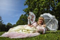 Frau im venetianischen Kostüm, das auf dem grünen Park mit weißem Regenschirm liegt Stockfotografie