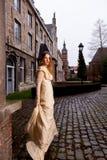 Frau im viktorianischen Kleid in einem alten Stadtplatz am Abend im Profil Stockfoto