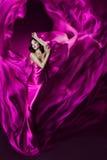 Frau im violetten wellenartig bewegenden silk Kleid als Flamme Stockbild
