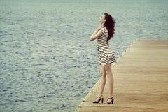 Frau im Weiß auf der Küste Stockbild