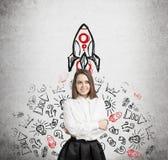 Frau im Weiß und in der Raketenskizze auf Beton Stockfoto