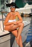 Frau im weißen Badeanzug, im Hut und in der Sonnenbrille, die recht an der Luxusyacht aufwirft Lizenzfreie Stockbilder