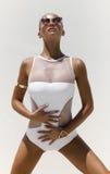 Frau im weißen Badeanzug und in der goldenen Sonnenbrille mit dem Haar wirft oben auf Hintergrund auf Hautecouture-Schuss Stockfotos