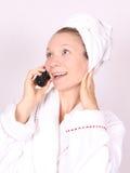 Frau im weißen Bademantel spricht am Telefon Stockbild