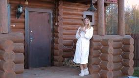 Frau im weißen Bademantel und in den Pantoffeln, mit Kaffee gehen auf das Portal ein Holzhaus stock video footage