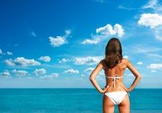 Frau im weißen Bikini in dem Meer. Hintere Ansicht. stockbild