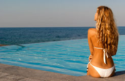 Frau im weißen Bikini, der nahe Unbegrenztheitspool sitzt Stockfotos