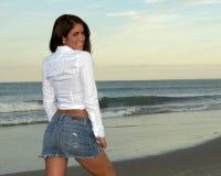 Frau im weißen Hemd und im Jean-Rock, die vorbei rückseitig schaut Lizenzfreie Stockfotos