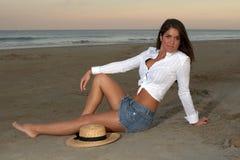 Frau im weißen Hemd und im Jean-Rock mit Strohhut Stockbild