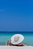Frau im weißen Hut, der auf dem Strand liegt Lizenzfreie Stockfotografie