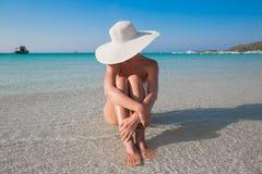 Frau im weißen Hut, der auf dem Strand sitzt Lizenzfreies Stockfoto