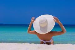 Frau im weißen Hut, der auf dem Strand sitzt Stockfotografie