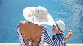 Frau im weißen Hut mit dem Bogen und kleinem Jungen, die zusammen am Rand des Swimmingpools sitzen