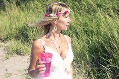 Frau im weißen Kleid auf dem Strand mit Getränk Lizenzfreies Stockfoto