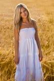 Frau im weißen Kleid auf Feld Stockbild