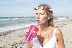 Frau im weißen Kleid, das auf dem Strand mit Getränk steht Stockfotos