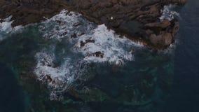 Frau im weißen Kleid, das sehr weit auf einem felsigen Ufer steht stock video footage