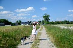 Frau im weißen Kleid mit Hund Lizenzfreie Stockfotografie