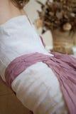Frau im weißen Kleid mit lila Gurt und Engel beflügeln in der Hand Lizenzfreie Stockfotografie