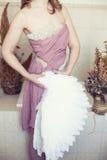 Frau im weißen Kleid mit lila Gurt und Engel beflügeln in der Hand Stockfotografie