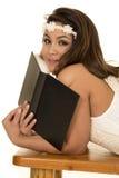 Frau im weißen Kleid und Stirnband legen mit dem Schwarzbuchschauen Stockbilder