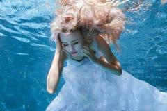 Frau im weißen Kleid unter Wasserpool Stockbild