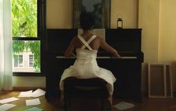 Frau im weißen Kleid, welches das Klavier spielt stockfotos