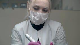 Frau im weißen Mantel über schwarzem Pullover hält Tätowierungsgewehr stock video footage